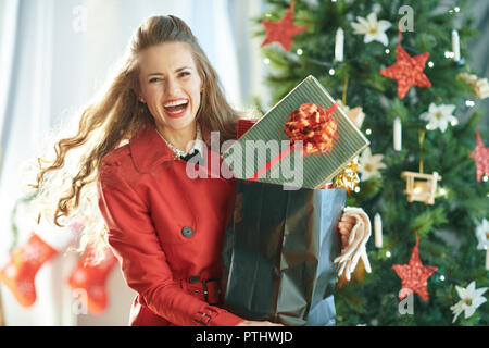 cheerful modern woman in red trench coat with shopping bag full of Christmas present boxes near Christmas tree - Stock Image