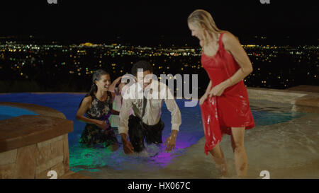 High angle selective focus view of laughing friends partying and playing in hot tub on balcony overlooking scenic - Stock Image