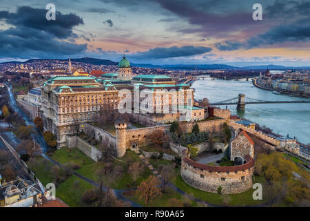 Budapest, Hungary - Aerial panoramic view of Buda Castle Royal Palace and Szechenyi Chain Bridge at dusk with colorful clouds and sky - Stock Image