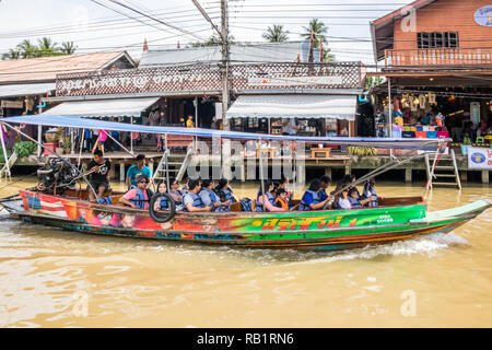 Amphawa, Thailand - 7th October 2018: A tour boat with Chinese touristsmakes its way up the river. A floating market is held every weekend. - Stock Image