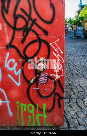 Cobbled Pavement scene In Mitte, Berlin. Colourful wall with tiny artwork disappearing under graffiti - Stock Image