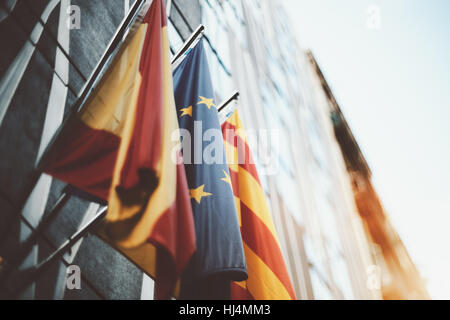 True tilt shift shooting of waving flags on modern business office facade in Barcelona: European Union, Catalonia, - Stock Image