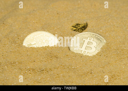 several bitcoin crypto coins on brilliant golden sand. finding and mining cryptocurrency - Stock Image