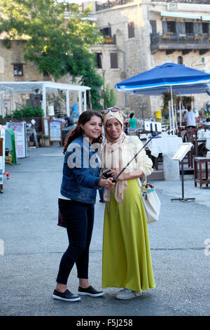 Young Muslim women friends taking a selfie photograph along the harbour front in Kyrenia Girne North Cyprus  KATHY - Stock Image