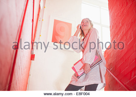 Smiling businesswoman holding folders and talking on cell phone in stairwell - Stock Image