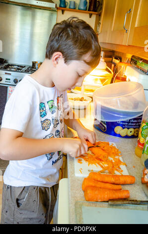 A young boy peeling carrots with a vegetable peeler on the kitchen worktop. - Stock Image