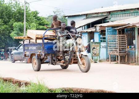 Adzopé , côte d'ivoire - June 10, 2017: a teenager on a motorcycle taxi with his friends and carrying boards with a disassembled bed - Stock Image