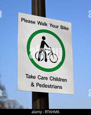 Safety Sign. 'Please Walk Your Bike. Take Care Children & Pedestrians'. K Village, Kendal, Cumbria, England, United Kingdom, Europe. - Stock Image