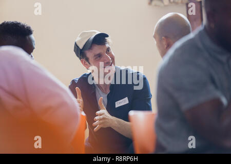Smiling man talking in group therapy - Stock Image