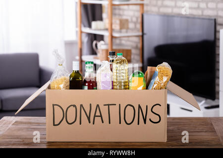 Various Food Items In Donation Box On Wooden Table - Stock Image