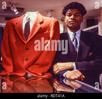 A shop assistant poses next to a stylish red jacket in a high end clothing shop in Manchester, England, Uk in 1989. - Stock Image