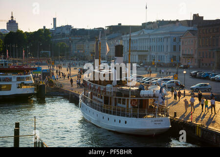 Helsinki harbor summer, sunset view of the Kauppatori waterfront area in Helsinki harbor with a Suomenlinna ferry boat at the quayside, Finland. - Stock Image