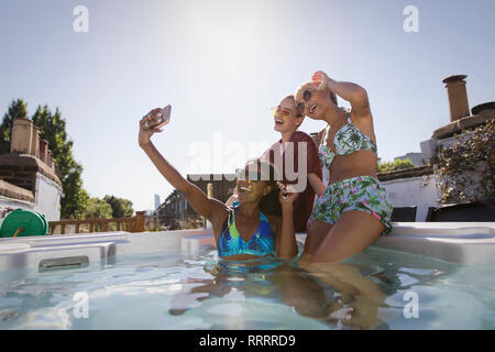 Happy, carefree young women friends in bikinis taking selfie with camera phone in sunny, rooftop hot tub - Stock Image