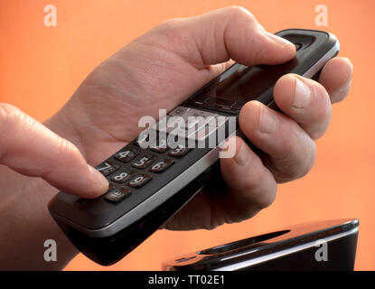 Man's hand holding a hands free landline telephone while pressing a number on the keypad to make a phone call. - Stock Image