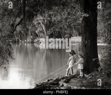 1960s LITTLE BOY AND GIRL FISHING HOLDING STICKS IN WATER BAYOU VEGETATION SPANISH MOSS HANGING FROM TREES - a7065 HAR001 HARS FRIENDSHIP FULL-LENGTH INSPIRATION MALES SERENITY SIBLINGS SISTERS B&W SUMMERTIME AND RECREATION LOUISIANA MOSS MOOD SIBLING SOUTHERN TIMELESS LITTLE SISTER STICKS BAYOU COOPERATION GROWTH JUVENILES TOGETHERNESS VEGETATION BIG BROTHER BLACK AND WHITE CAUCASIAN ETHNICITY HAR001 OLD FASHIONED - Stock Image