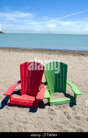 Muskoka chairs partially submerged in water and sand after springtime floods and high lake waters in Toronto, Ontario, - Stock Image