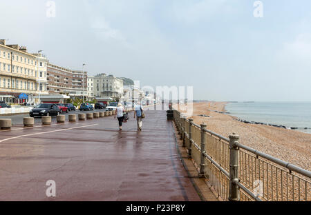 Couple walking along the promenade and Beach, Hastings, East Sussex, England , UK - Stock Image