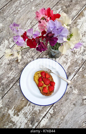 UK. Summer breakfast outside in the garden - a plate of strawberries on French toast, with a jar of freshly picked sweet peas on an old wooden table - Stock Image