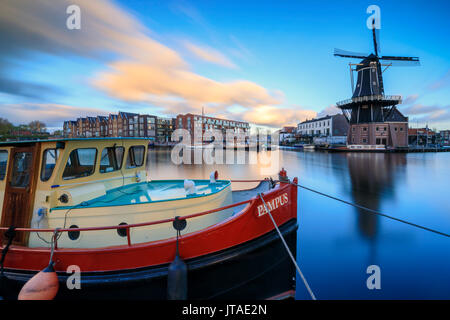 The fishing boat frames the Windmill De Adriaan reflected in the River Spaarne at dusk, Haarlem, North Holland, The Netherlands - Stock Image