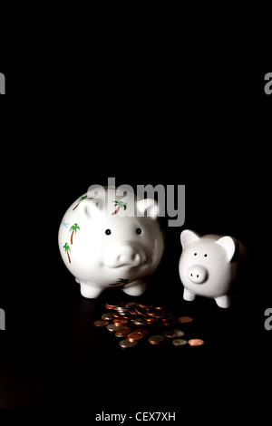 Honeymoon savings Piggy Bank with a small piggy bank and cash on a black background - Stock Image