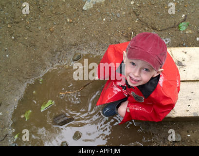 Boy playing in mud puddle, Underhill, Vermont, USA - Stock Image