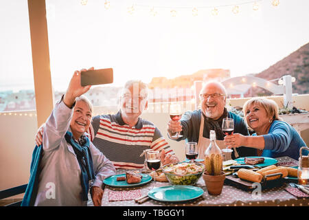 Happy seniors friends taking selfie with mobile smartphone camera at barbecue dinner - Mature people having fun eating and drinking red wine on patio  - Stock Image