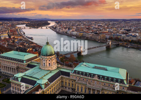 Budapest, Hungary - Aerial view of Buda Castle Royal Palace with Szechenyi Chain Bridge, Parliament and colorful clouds at golden sunrise - Stock Image