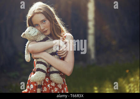 Portrait serene tween girl with stuffed animal in park - Stock Image