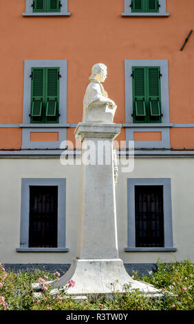 Classical marble statue on a plinth against a colourful salmon-coloured wall in Fivizzano, Tuscany, Italy. - Stock Image