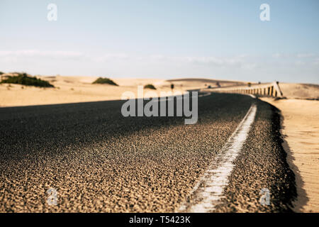 Ground close up point of view of black asphalt long road with desert sand dunes on the sides - travel and explore destination alternative summer holid - Stock Image