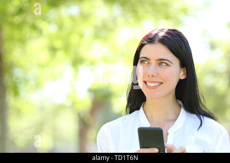 Front view portrait of a happy adult woman holding smart phone and thinking looking at side in a park - Stock Image