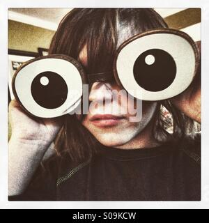 Boy with giant wooden eyes - Stock Image