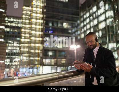 Businessman with headphones using digital tablet on urban pedestrian bridge at night - Stock Image