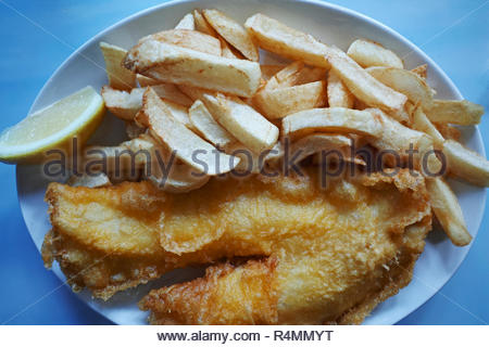Fish and chips: A plate of battered cod and chips with a slice of lemon. - Stock Image