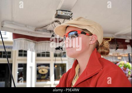Happy, young female coachman horse driver for horse-drawn taxi on Mackinac Island, Michigan, USA, where no cars or motorized vehicles allowed. - Stock Image