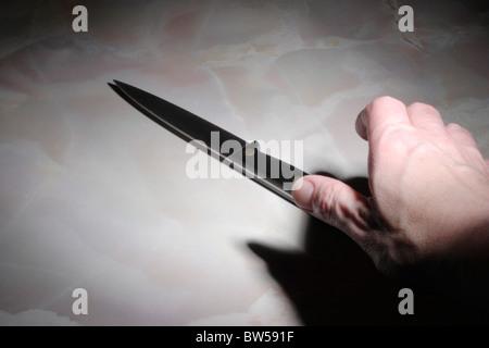 Hand reaching for kitchen knife, spotlit - Stock Image