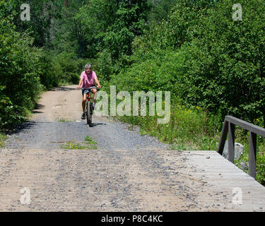 Senior woman riding a bicycle on a dirt and gravel road in the Adirondack Mountains, NY USA - Stock Image