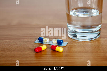 medicinal capsules and a glass of water on the table indoor closeup - Stock Image
