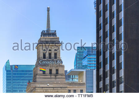 Rainbow flag waving on top of the Canada Life Building in the downtown district. June is celebrated as Pride Month in the Canadian city capital of the - Stock Image