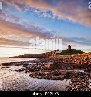 Dunstanburgh Castle, now a ruin, commanding the beach at Embleton Bay, Northumberland, England, under a dramatic dawn sky. - Stock Image