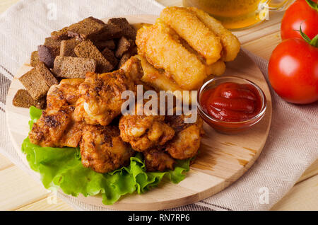 Beer snack, chicken wings, roasted cheese and toast on a kitchen board - Stock Image