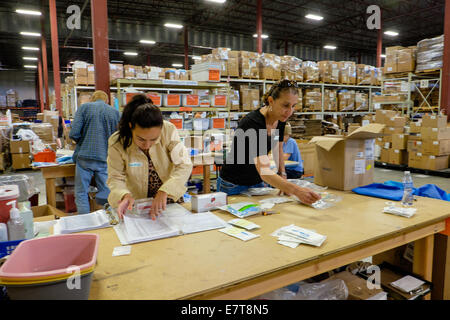 Centennial, Colorado USA. 23 September 2014.  Camelia Kamm looks up the bin number for medical supplies while Maya - Stock Image
