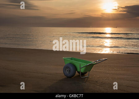 Green beach cart on the beach at sunrise, Virginia Beach, Virginia - Stock Image