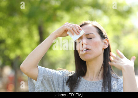 Stressed woman drying sweat using a wipe in a warm summer day in a park - Stock Image