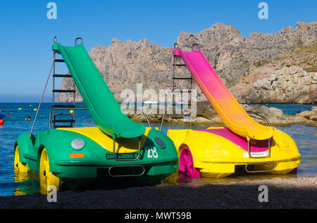 Two brightly coloured pedalos parked on a beach in Cala San Vicente in Mallorca, Spain. - Stock Image