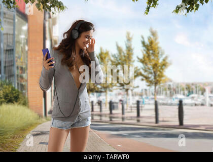 Young woman listening to music on headphones - Stock Image