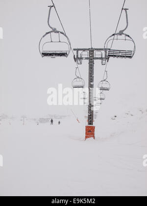 chair lift and piste  in the french alps with heavy falling snow - Stock Image
