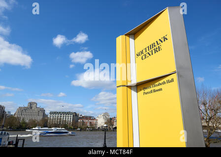 Southbank Centre yellow information sign directing to the entrance of Queen Elizabeth Hall and Purcell Room. Thames in the background with Clipper boa - Stock Image