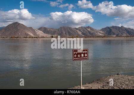 Safety warning sign on the bank of the River Yarlung Tsangpo (Brahmaputra), west of Lhasa, Tibet, China - Stock Image