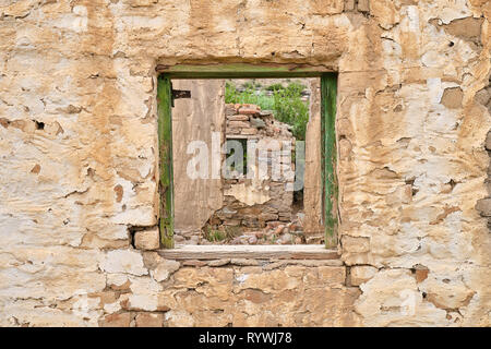 Central empty green window frame on rocky wall of abandoned house.  Through frame see crumbled walls of remaining ruined house - Stock Image